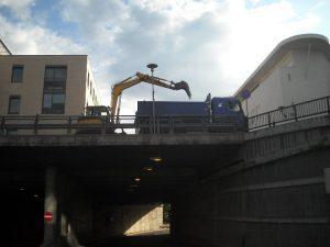 gravemaskin og lastebil på bro